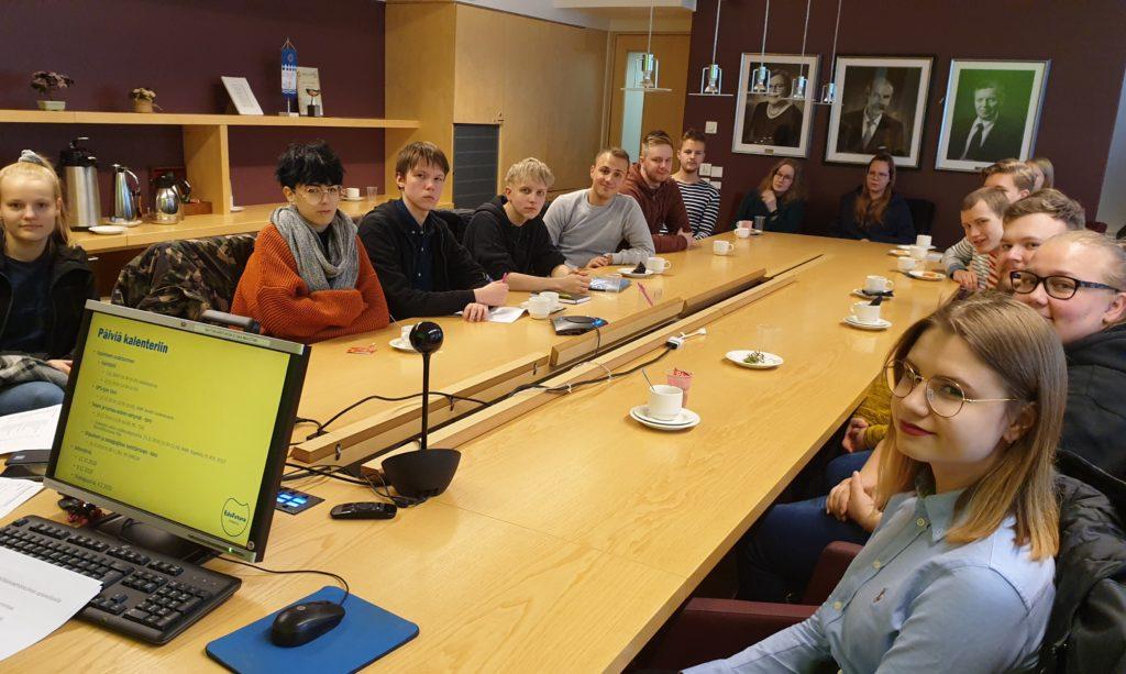 Opiskelijoita istuu kokouspöydän ympärillä.