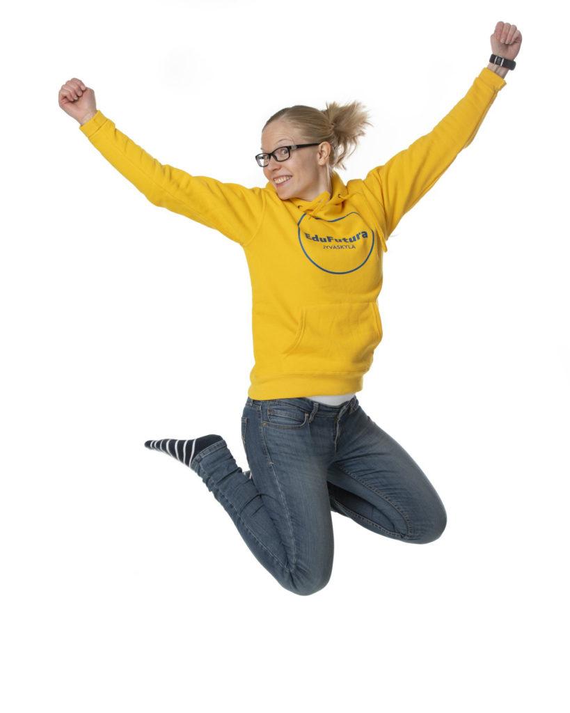 Koulutussuunnittelija Outi Ruusuvirta-Uuksulainen hyppää ilmaan keltaisessa EduFutura-hupparissa