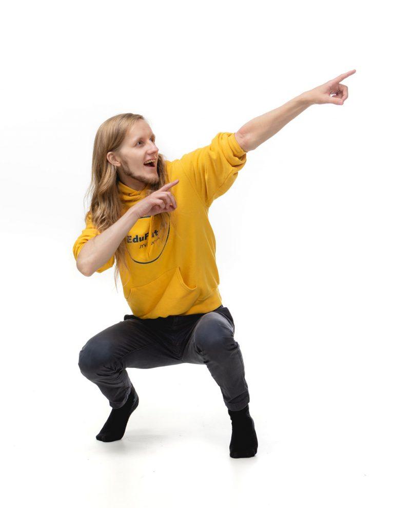 Mies kyykyssä osoittaa käsillä ylös