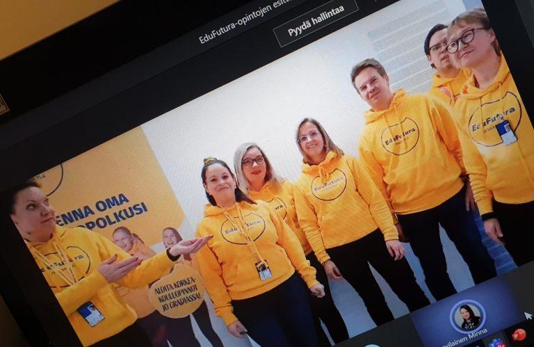 Naisia ja miehiä keltaisissa huppareissa seisomassa rivissä