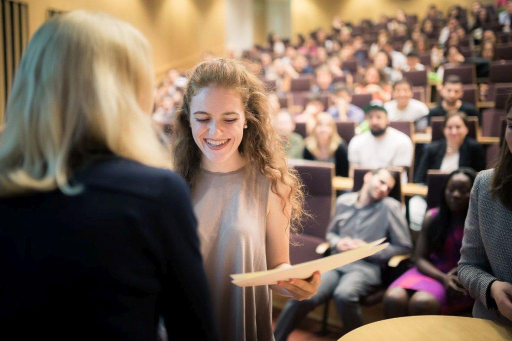 Naiselle ojennetaan todistusta, taustalla yleisöä auditoriossa.