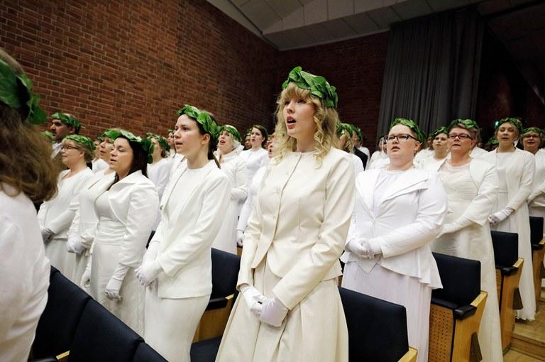 Yliopiston promootiossa naisia ja miehiä seppeleet päässä