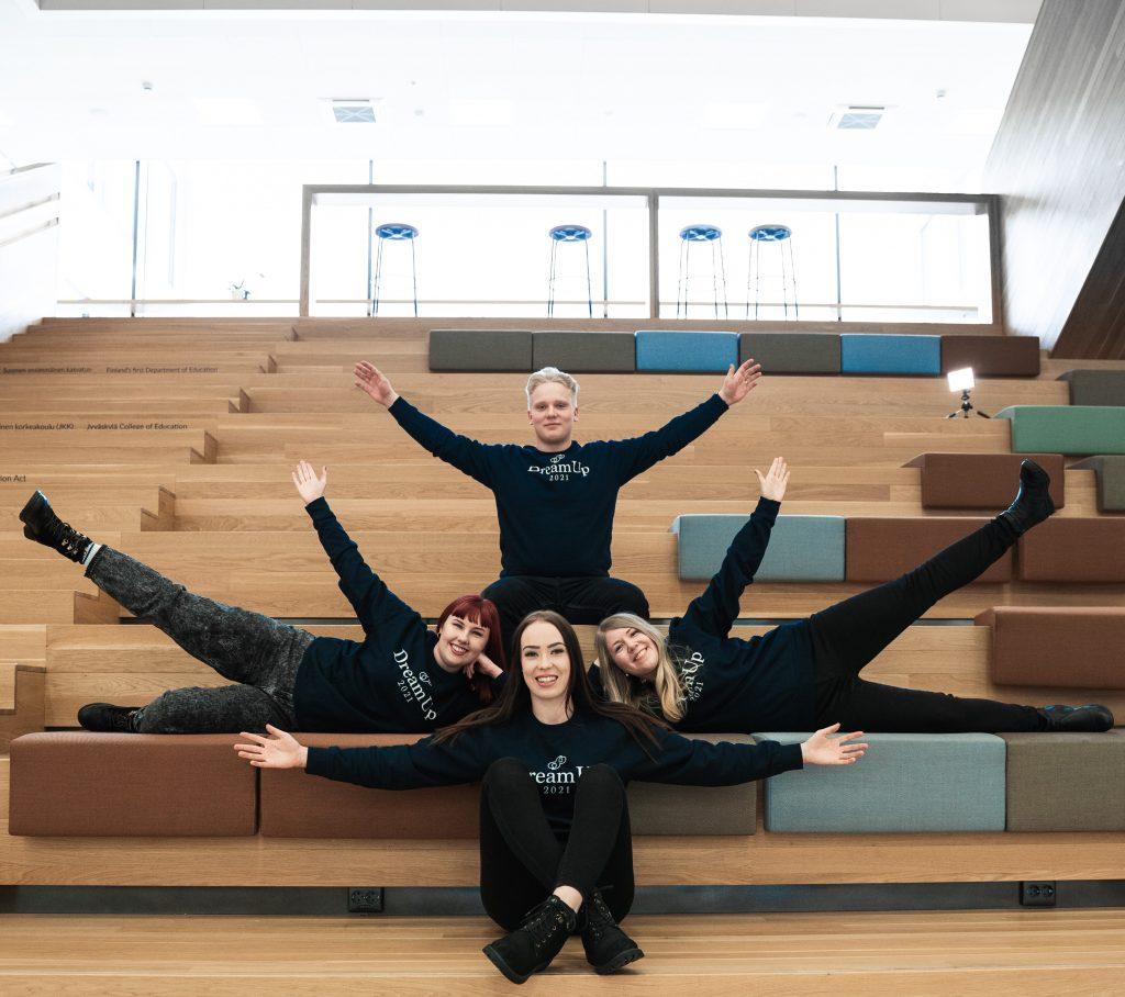 neljä opiskelijaa viitoilevat käsillä Ruusupuiston portaissa. Kuva Joel Tiainen.